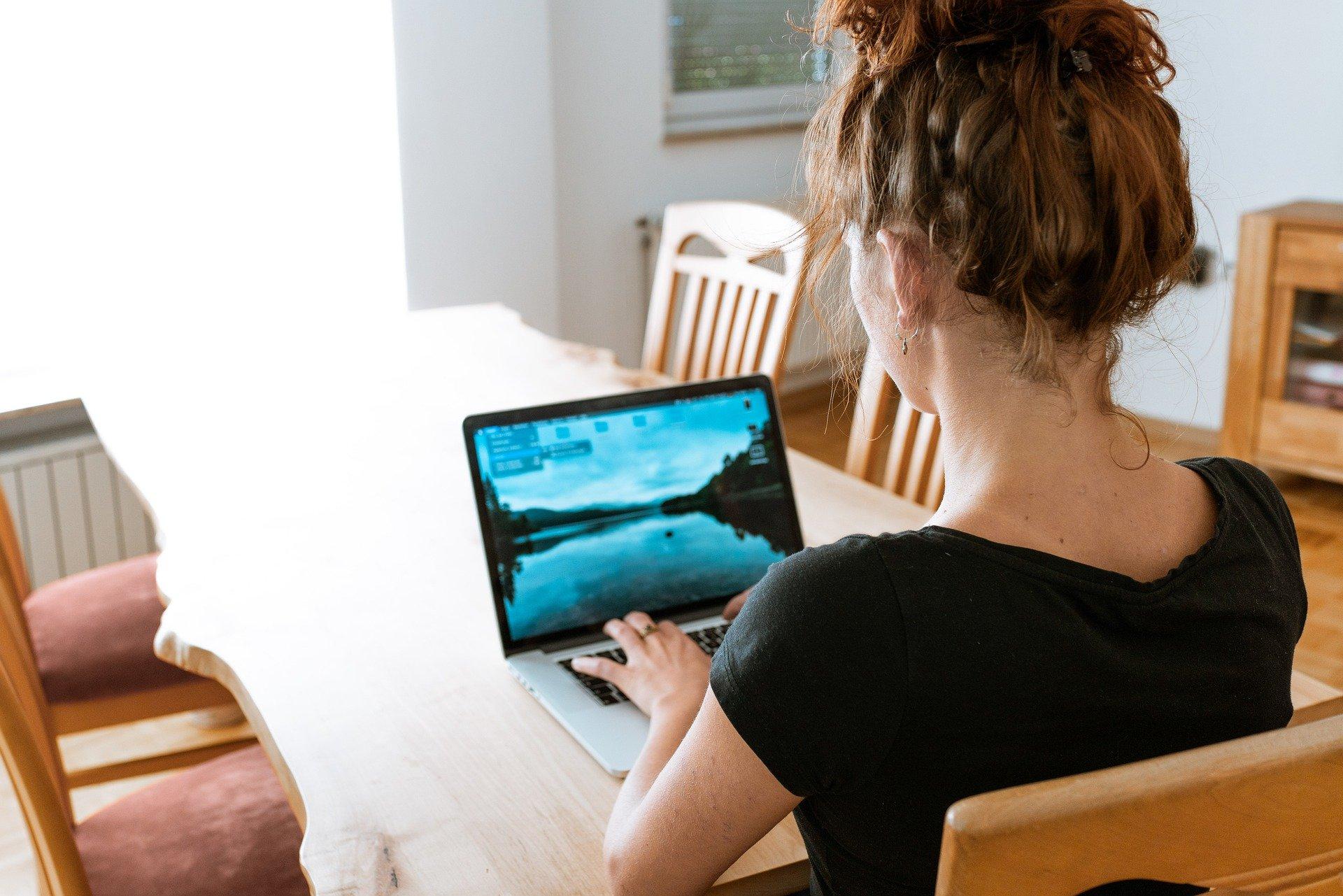 Bild von Person in einem offensichtlichen Esszimmer bei der Remote-Arbeit am Esstisch